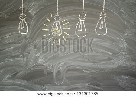 idea concept - row of light bulbs with glowing one on blackboard with copy space