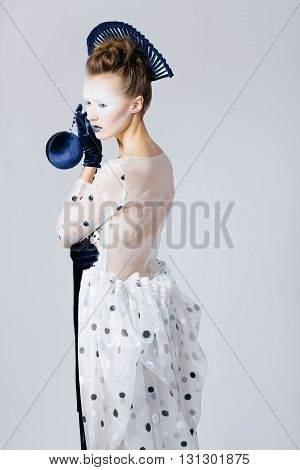 Creative shocking portrait of Japanese young woman in fashion elegant designers grey dress and blue velvet gloves on grey blackground