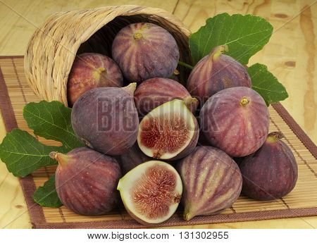 pouring out figs from wicker basket .