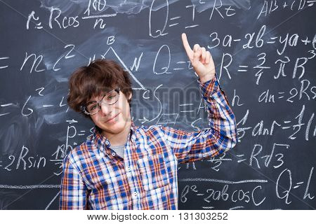 Boy in glasses blackboard filled with math formulas in background