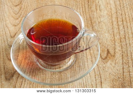 A cup of tea in a transparent cup, displayed on a table top.