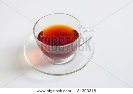 A cup of tea in a transparent cup, displayed on a white background.