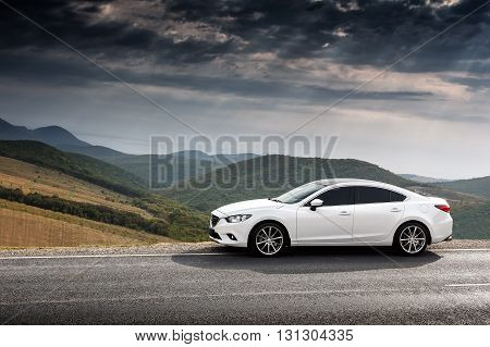Krasnodar, Russia - September 07, 2014: White Car Mazda 6 parked at countryside asphalt road near green mountains at daytime