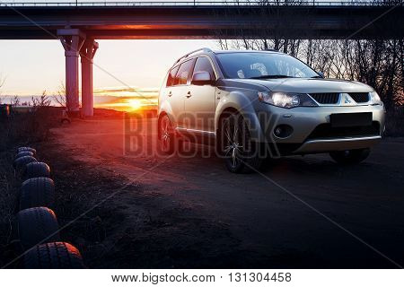 Saratov, Russia - November 27, 2014: Car Mitsubishi Outlander on countryside road near bridge at sunset