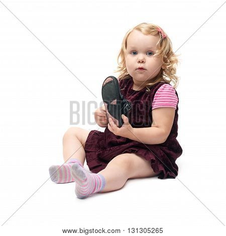 Young little girl with curly hair in purple dress sitting and putting shoes over isolated white background