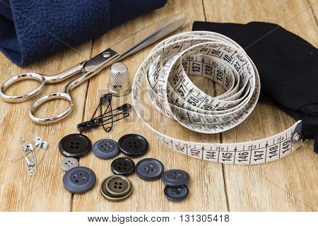 Sewing tools and sewing kit on a wooden background