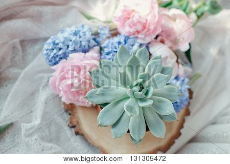 floral arrangement on a wooden stump pink peony and hyacinth