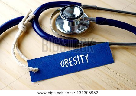Medical Conceptual Image With Obesity Word Written On Label Tag And Stethoscope On Wooden Background