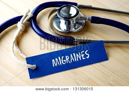 Medical Conceptual Image With Migraines Word Written On Label Tag And Stethoscope On Wooden Backgrou