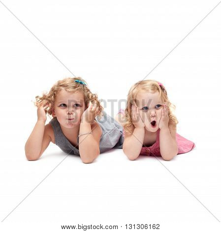 Couple of young little girls sinsters with curly hair in gray and pink dress lying over isolated white background