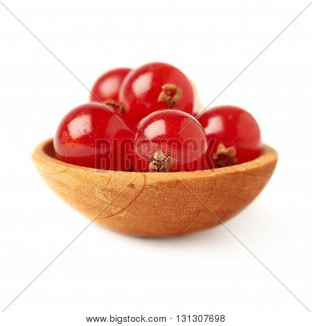 Wooden spoon filled with ripe Red Currant berries isolated over white background