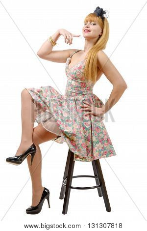 beautiful girl in colorful dress sitting on a stool isolated on white background
