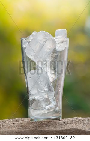 ice in the glass on sand ground