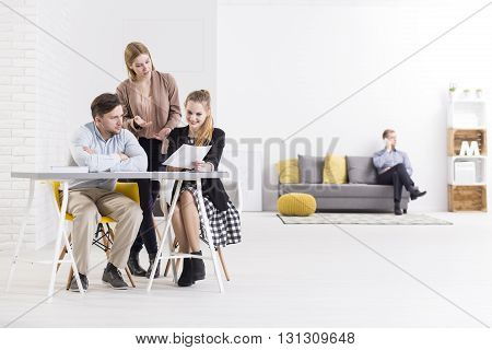 Three young people working together on a new business plan in company. In the background young man sitting on sofa and talking the phone