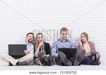 Young Working People Sitting By The Wall