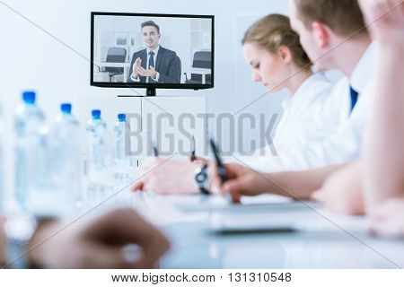 Young handsome businessman giving advice during video conference online with management of company