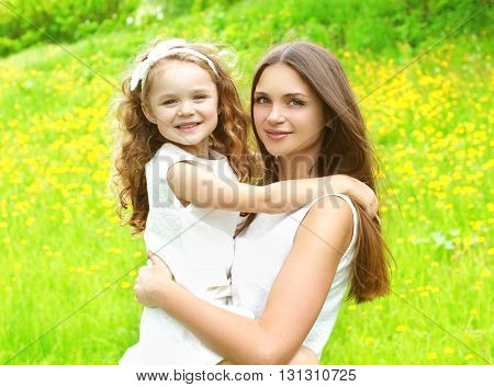 Happy Mother And Daughter Child Hugging In Summer Day