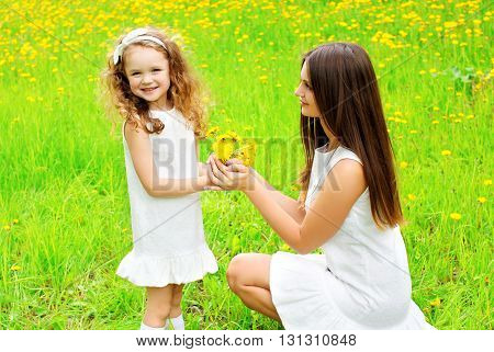 Mother And Daughter Child With Yellow Dandelion Flowers In Summer Day