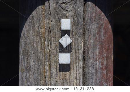 three sugar lumps on grey beam close up