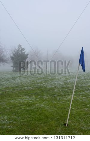 Forlorn looking flag on an empty golf course on a cold and foggy day