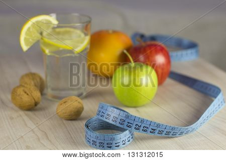 group of diet fruits and welnuts with water and blue measure tape
