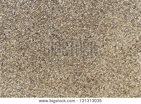 Exposed aggregate concrete in close-up made of small pebbles in different brown and gray color shades