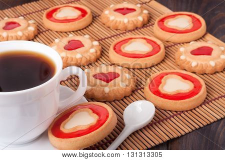 cookies with jelly and a cup of coffee on a bamboo napkin.