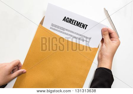 Concept of Businesswoman opening agreement document in envelope.