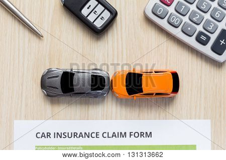 Top view of car insurance claim form with car toy on wooden desk concept