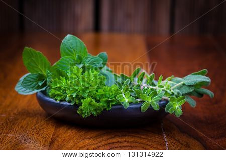 Fresh herbs from garden on wooden table