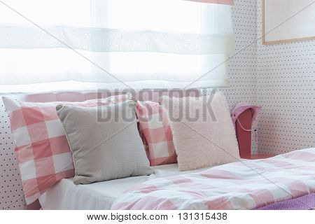 pillows on bed in pink color tone bedroom design