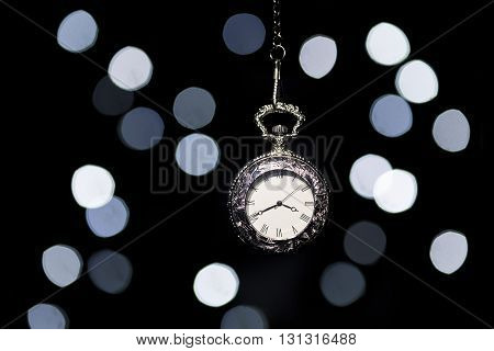 Silver pocket watch hang in front of a bokeh background