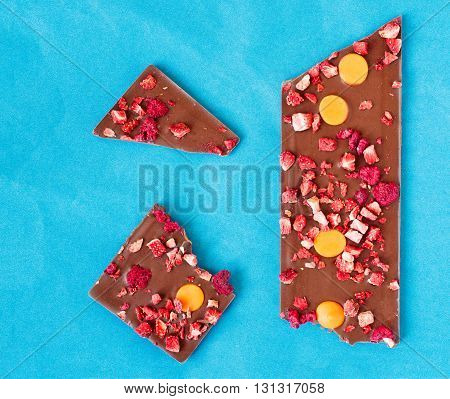 Top view of an orange strawberry and raspberry milk chocolate tablet broken in three pieces on a light blue background.