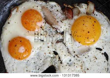 Detail of the fried eggs with bacon on the pan - a hearty breakfast