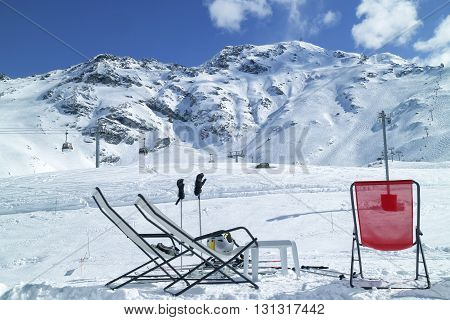 Apres ski at high Alps mountains winter resort of Les Arcs. Red and white relaxing lounge chairs on snow in front of ski slopes and lifts.