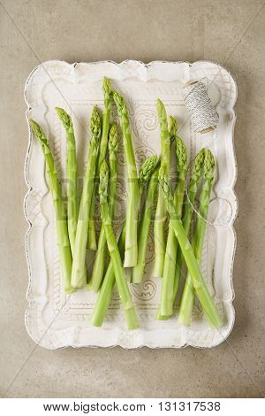 Fresh uncooked green asparagus stalks on stone surface