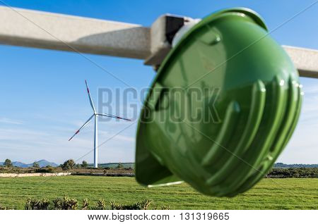 Wind turbines blades on the countryside and  protection helmet