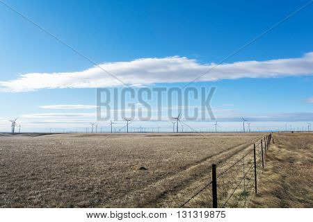 A wind farm works in a dry grass field under a cloudy sky.