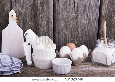 Still life on a kitchen wooden table with white ceramic molds for baking, eggs, flour and other kitchen utensils. The concept of simple healthy home cooking.