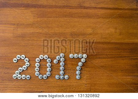 New Year 2017 made of screws on the old vintage wooden background