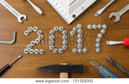 New Year 2017 made of screws on the old vintage wooden background. screwdriver angle drill wrench knife hexagon hammer