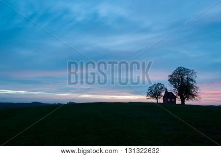 A liitle lonely chapel on a small hill surrounded by two trees at a beautiful sunset