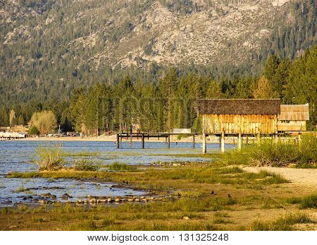 Boat houses overlooking an alpine lake with people and birds in the background enjoying the water