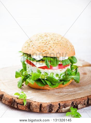 Vegetarian burger with egg and pea patty, fresh salad, tomato slice on a cutting wooden board