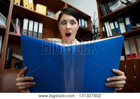 Surprised pretty woman looking at open folder.