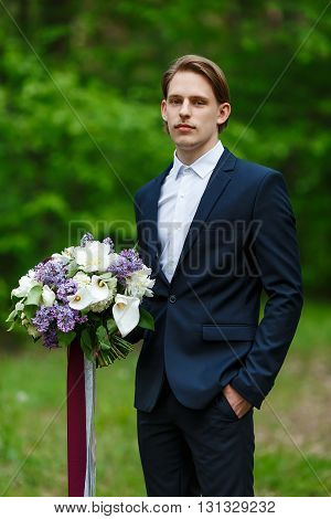 Young beautiful groom standing and holding wedding bouquet.