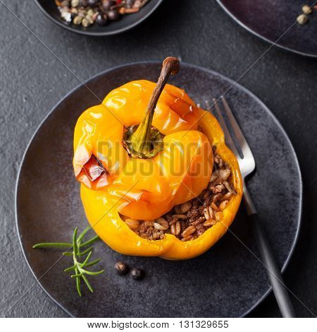 Baked stuffed bell peppers filled with spelt wheat, rice, vegetables on a dark plate stone background
