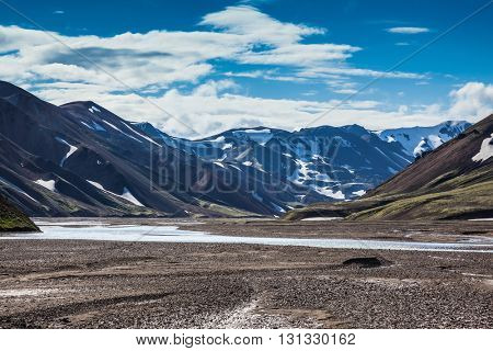 Rhyolite mountains surround the flat valley Park Landmannalaugar. Valley cross streams and rivers of meltwater