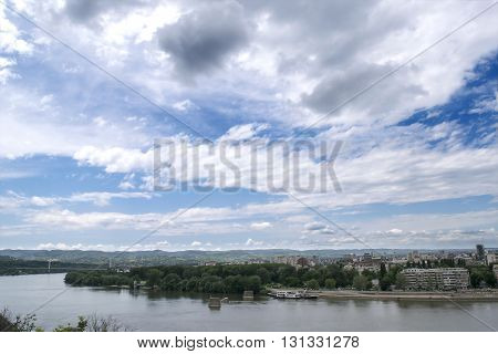 Landscape, dramatic sky and a view on a Danube river and a city