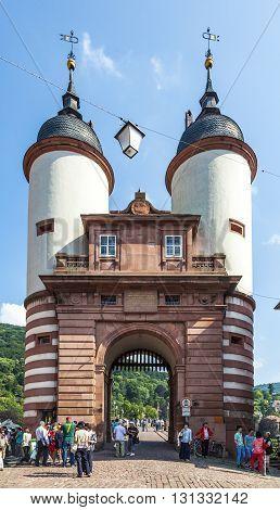 People Visit Bridge And Town Gate Of Heidelberg, Germany